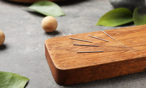 Board with needles for acupuncture on dark table